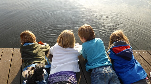 Four children playing together on a dock