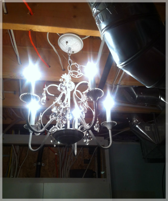 A chandelier hanging from the rafters in the laundry room. Poster by Bergen and Associates.