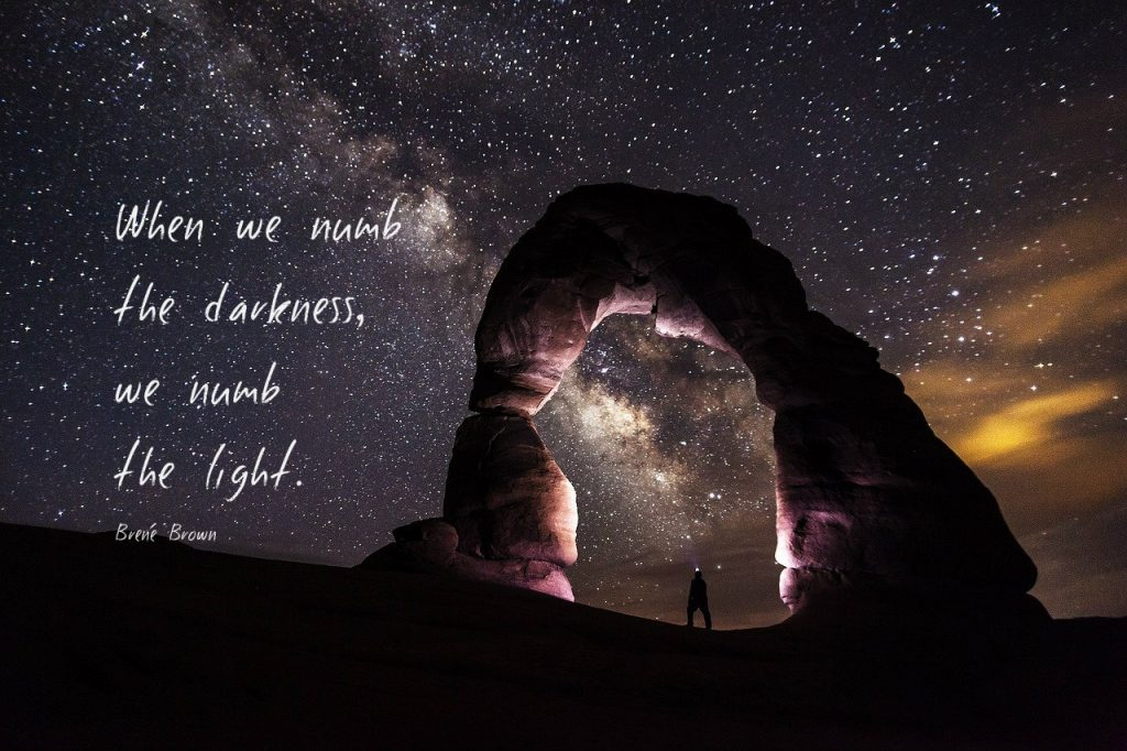 When we numb the darkness, we numb the light. Quote by Brene Brown. Pic of starry sky with beautiful arch.