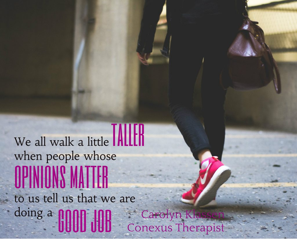 Poster of a woman walking on parking lot. Carolyn Klassen quote: We all walk a little taller when people whose opinions matter to us tell us that we are doing a good job.. On post about how Husband makes my life better.