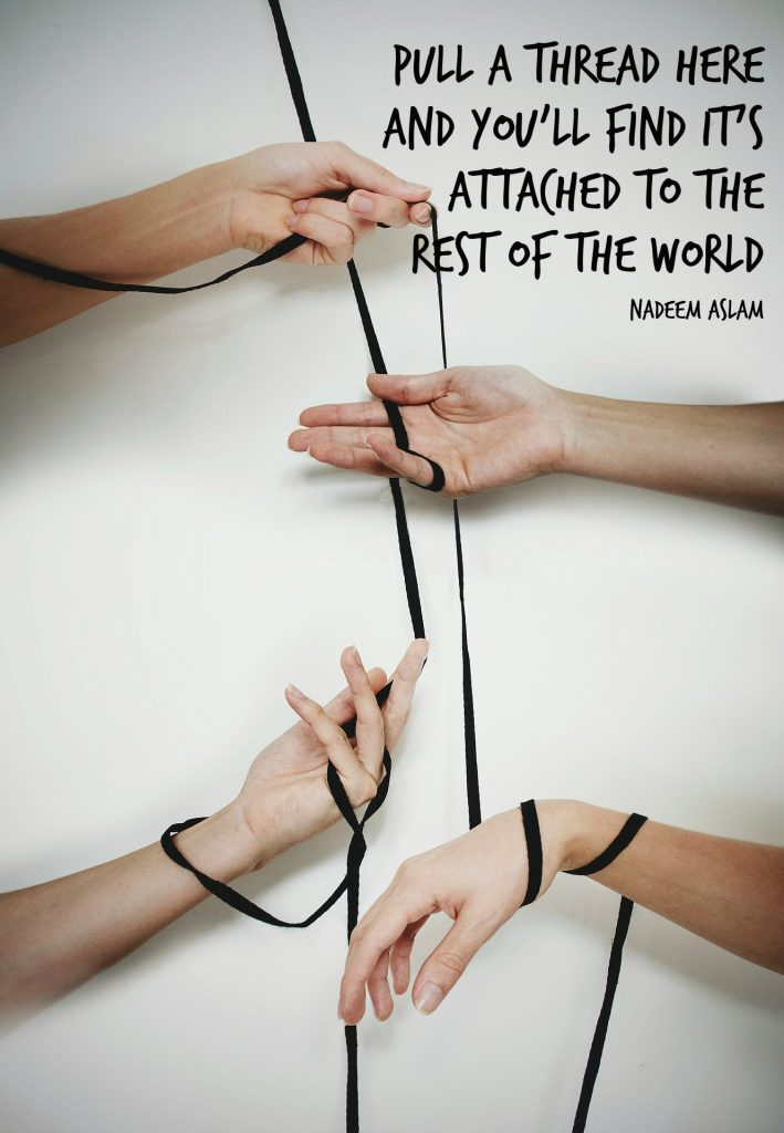 Pull a thread here and you'll find it's attached to the rest of the world. Quote by Nadeem Aslam on picture of hands interconnected by ribbon. Poster by Carolyn Klassen of Conexus Counselling