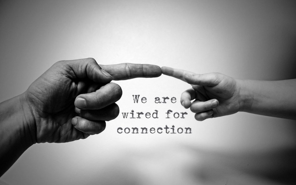 We are wired for connection. Two hands extended to reach to each other on blog about zielschmerz