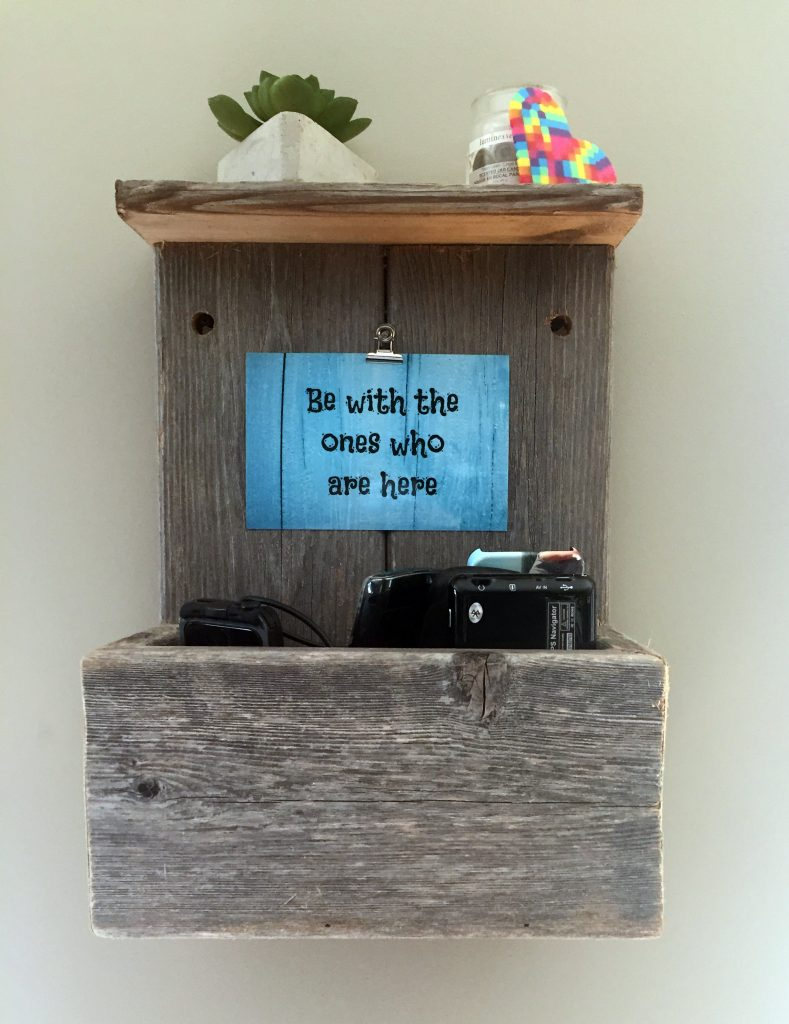"Picture of a cell phone holder ""Be all here"" cell phone catcher reminds us to put our cell phones here and be fully present with the ones we love. PIc of a catcher made of barnwood style wood"