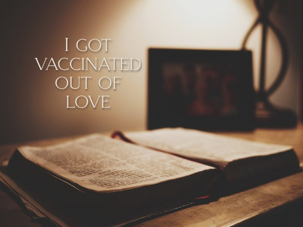 I got vaccinated out of love. Picture has open Bible. On article about a theology of vaccination